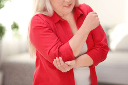 Mature woman suffering from elbow pain at home