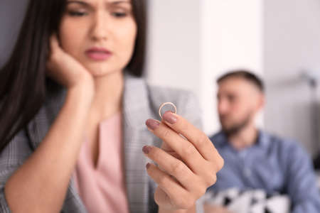 Sad woman with wedding ring and her husband on background. Time to visit family psychologist