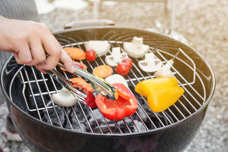 Man cooking juicy vegetables on barbecue grill Stock Photo