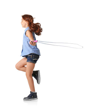 Cute little girl playing with jumping rope on white background