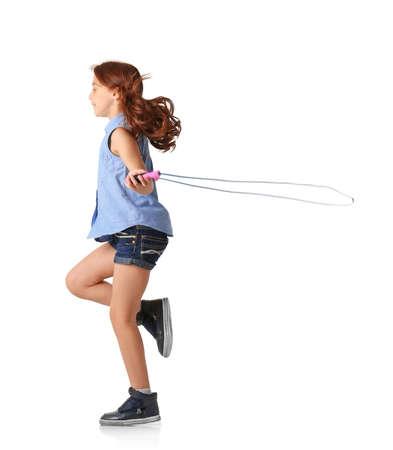 Jolie petite fille jouant avec la corde à sauter sur fond blanc