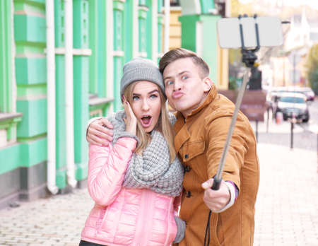 Young adorable couple taking selfie outdoors