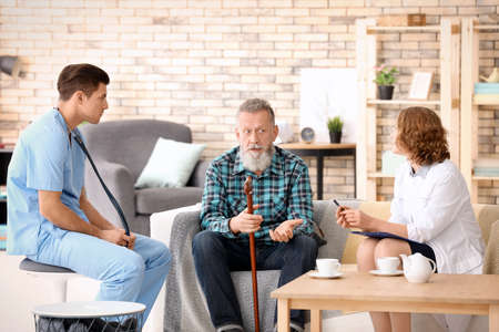 Senior man and young caregivers sitting on sofa at home