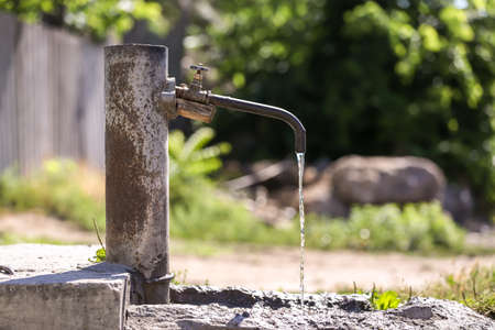 Tap with pouring water outdoors. Water scarcity concept Stock Photo