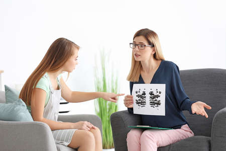 Young woman passing Rorschach test at psychologists office