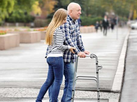 Jeune femme aidant un homme âgé avec déambulateur pour traverser la route