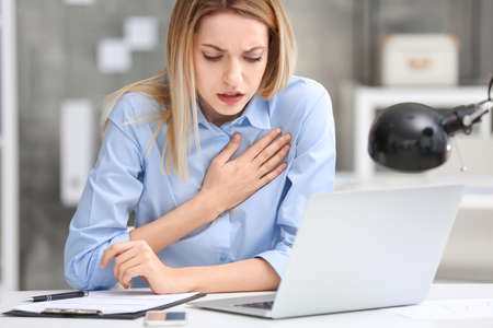 Young woman suffering from chest pain in office Banque d'images