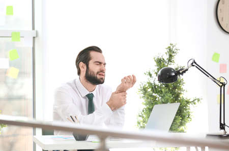 Young man suffering from wrist pain in office Stock Photo
