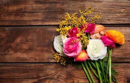 Beautiful ranunculus and mimosa flowers on wooden background