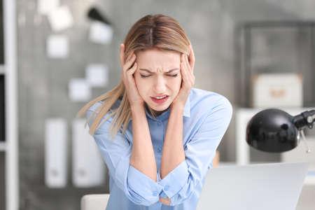 Jonge vrouw die aan hoofdpijn in bureau lijdt Stockfoto