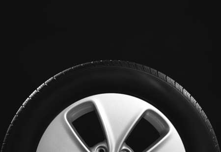 Car tire with rim on black background, closeup