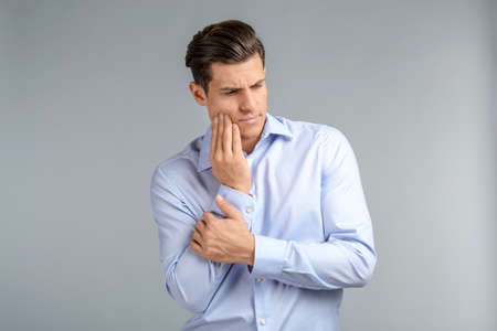 Young man suffering from toothache on grey background Фото со стока