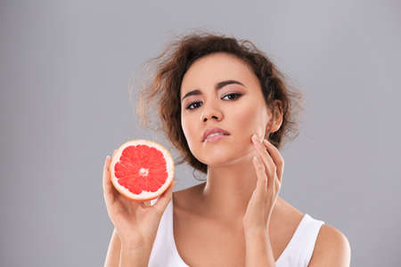 Beautiful young woman with acne problem holding grapefruit on grey background. Skin allergy