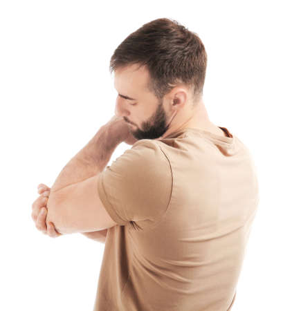 Young man suffering from pain in elbow on white background