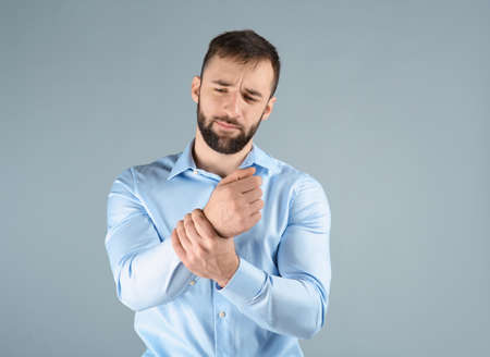 Young man suffering from pain in wrist on light background