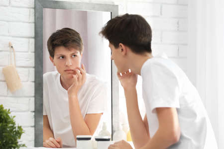 Teenage boy with acne problem looking in mirror at home Standard-Bild
