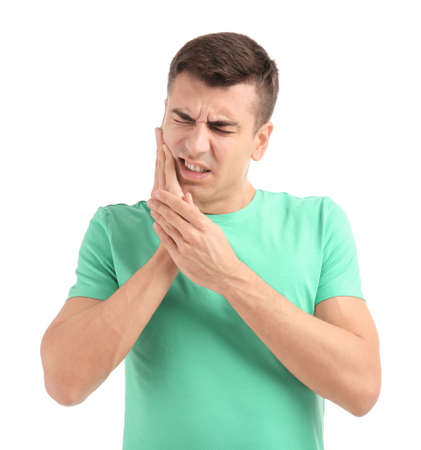 Young man suffering from toothache on white background