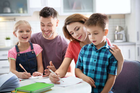 Little children with parents doing homework at home