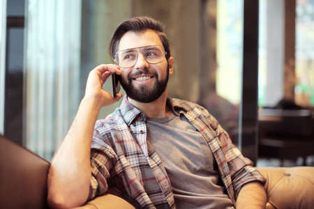 Handsome trendy hipster talking on mobile phone in cafe