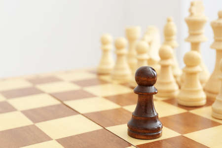 Wooden chess figures and one different on board Standard-Bild