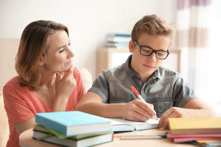 Teenager with mother doing homework at home Stock Photo
