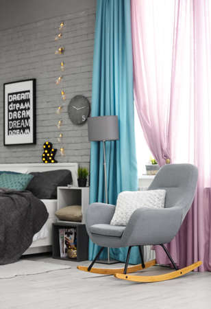 Elegant room interior with comfortable bed and rocking chair