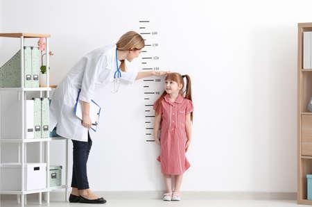 Medico femminile che misura l'altezza della bambina in clinica