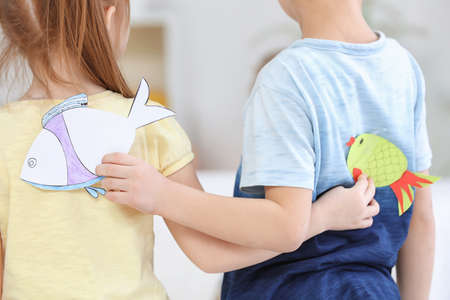 Little children sticking paper fish on each other indoors. April fools day prank Stock Photo