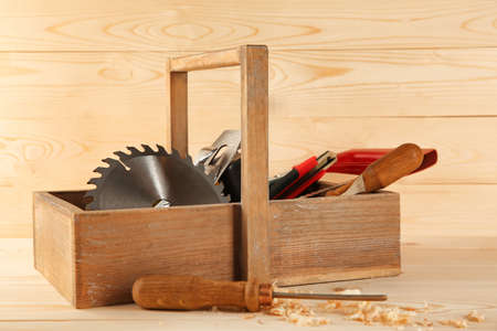 Box with carpenter's tools on wooden background