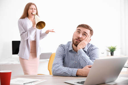 Angry boss with megaphone screaming at employee in office