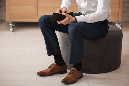 Man with wallet wearing new shoes indoors