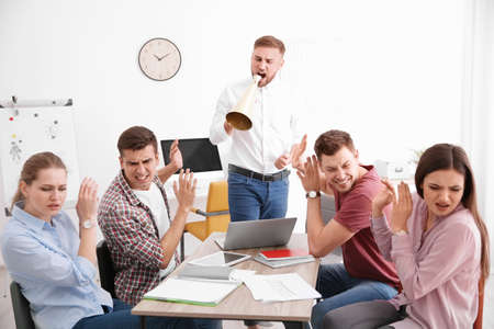 Angry boss with megaphone screaming at employees in office