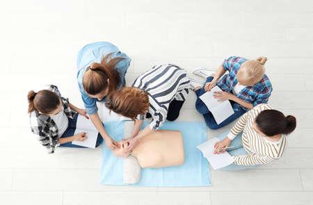 Grupa osób wykonujących RKO na manekinie na zajęciach pierwszej pomocy