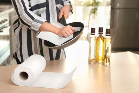 Woman wiping frying pan with paper towel indoors