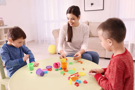 Nanny and little boys sculpting from plasticine at home Stock Photo