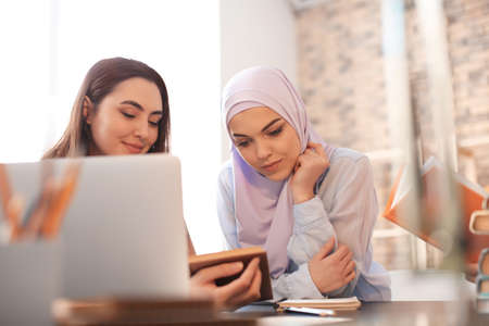 Female student with her Muslim classmate in library Reklamní fotografie
