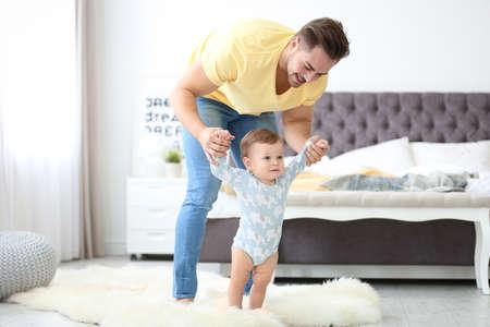 Bebé dando los primeros pasos con la ayuda del padre en casa Foto de archivo
