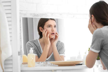 Teenager-Mädchen mit Akne-Problem, das in Spiegel drinnen schaut