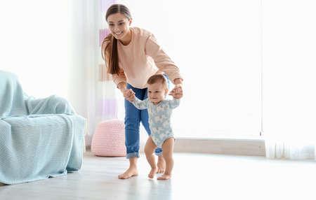 Baby macht erste Schritte mit der Hilfe der Mutter zu Hause