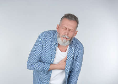 Man suffering from chest pain on light background