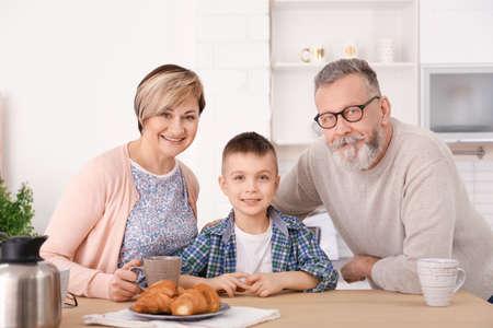 Feliz pareja senior desayunando con su nieto en casa Foto de archivo