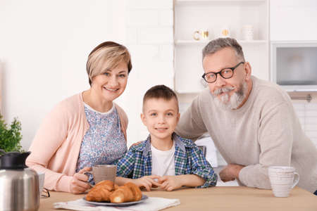 Happy senior couple having breakfast with little grandson at home Stock Photo