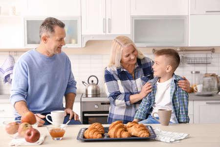 Happy senior couple having breakfast with little grandson in kitchen