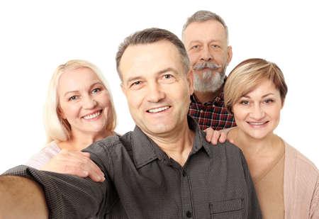 Group of happy senior people taking selfie on white background