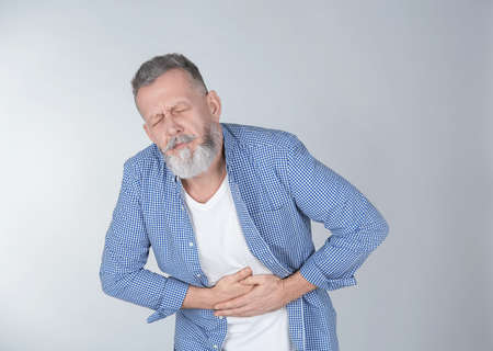Man suffering from abdominal pain on light background