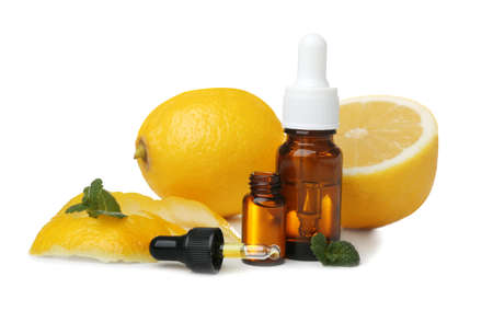Composition with bottles of lemon essential oil on white background