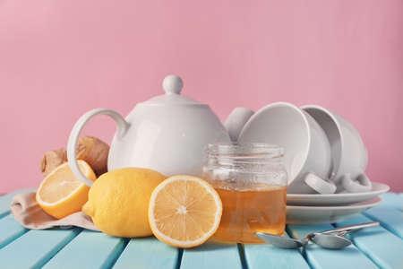 Lemons, jar with honey and crockery on table