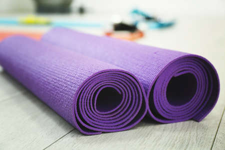 Rolled yoga mats indoors, closeup. Physiotherapy center Stock Photo