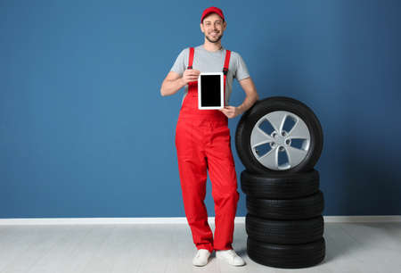 Male mechanic in uniform with car tires and tablet computer on color wall background
