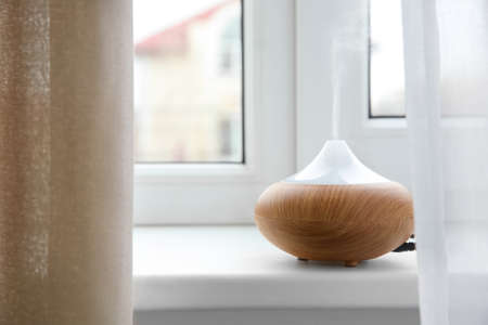 Aroma oil diffuser on window sill Stock Photo
